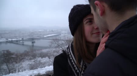 contato com os olhos : Beautiful young woman with teeth braces and man looking into each others eyes near river in winter clothing. Happy couple in love enjoy time together. Winter leisure outdoors