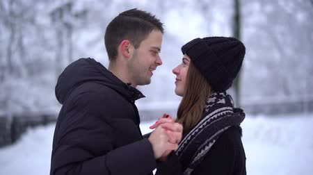 нежный : Beautiful young woman and man kissing in winter park under falling snow. Happy couple in love enjoys time together. Winter leisure. Slow motion.