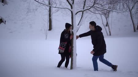 megragad : Happy smiling girl running from her boyfriend and hiding behind tree. Young man catches his girlfriend, grabs her and both fall in snow. Happy cute couple in love enjoy time together. Winter leisure