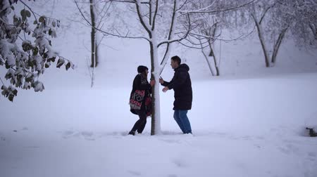 vállkendő : Cute young man and girl spend their leisure time in a snow-covered park. Date of young couple. Stock mozgókép