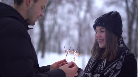 bengália : girl and a guy with sparklers in a snow-covered park. Stock mozgókép