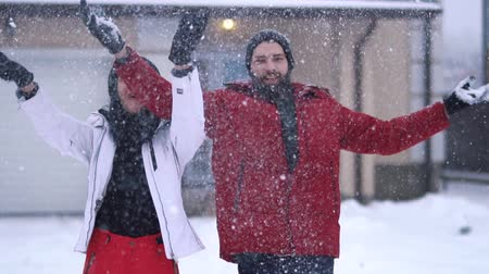 elevação : Bearded man throws handful of snow up, woman standing near raises hands. Happy young couple have a fun in winter backyard. Snow is falling. Concept of outdoor recreation