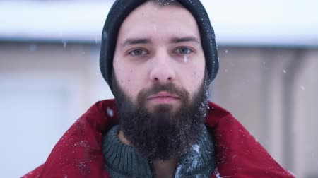 beardie : Portrait of calm bearded man looking in camera close up. Big snowball flies and crashes on the face of a man. Beardie is surprised. Concept of outdoor recreation and fun. Shooting in slow motion