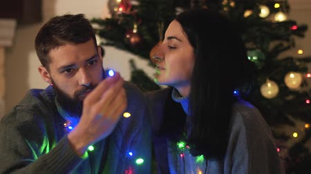 beardie : Man and woman sitting near new year tree with a garland around the neck. Girl caress hair of her boyfriend, beardie kiss her cheek. Happy adult couple have christmas fun. Concept of leisure at home