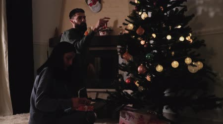 x mas : Man and woman in home clothes decorating new year tree at home. Woman corrects bow on small gift box. Happy couple prepare for Christmas party in dark room. Concept of leisure at home before holidays Stock Footage