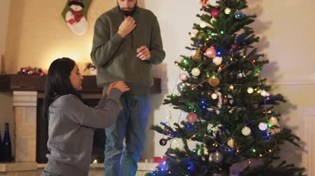 darovat : Young positive couple decorating the Christmas tree together in the room before holiday. The women giving toys to the man who hanging them on the fir tree. New Year and Christmas time concept. Happy family preparing for holidays
