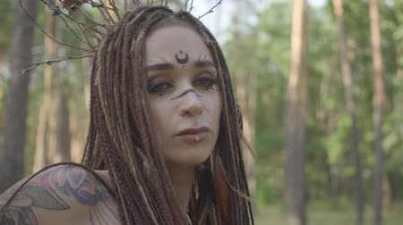 manó : Attractive dryad or forest fairy with afro-braids and tattoos on the body dancing in beautiful costume. The ancient ritual of forest creature. Performance of dancer in forest Stock mozgókép