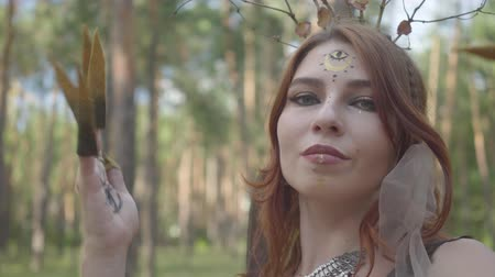 mitologia : Portrait of beautiful young woman in theatrical costume and make up of forest nymth belly dancing in forest showing perfomance or making ritual Vídeos