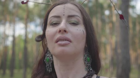 make up artist : Portrait of beautiful young woman in theatrical costume and make up of forest nymth belly dancing in forest showing perfomance or making ritual Stock Footage