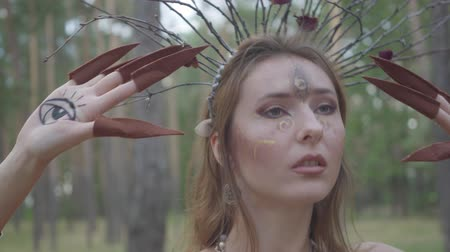 ninfa : Portrait of an attractive dryad or forest fairy with a wreath of branches on her head dancing under the trees. The ancient ritual of forest creature. Performance of dancer in forest
