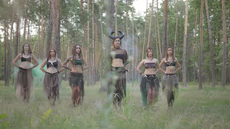 mythologie : Group of women dancers with make-up and in mystical fabulous costumes dancing groovy dance in the forest. Forest fairies, dryads have fun among the trees. Performance of dancers outdoor.