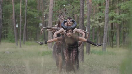 szatan : Group of women dancers with make-up and in mystical fabulous costumes dancing groovy dance in the forest. Forest fairies, dryads have fun among the trees. Performance of dancers outdoor.