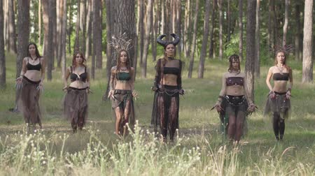 ninfa : Beautiful young women in theatrical costumes of devil or maleficent dancing belly dance in forest showing perfomance or making ritual Vídeos