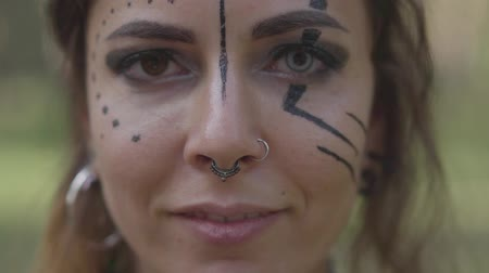 manó : Close-up portrait of an attractive woman with different color eyes and piercing in her nose looking in the camera. Performance of dancer in the forest Stock mozgókép