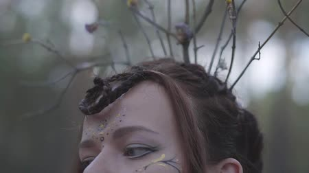 manó : Portrait of an attractive dryad or forest fairy with a wreath of branches on her head and painted the third eye on the forehead dancing under the trees. The ancient ritual of forest creature