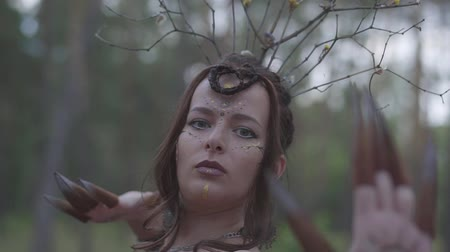 когти : Portrait of an attractive dryad or forest fairy with a wreath of branches on her head and painted the third eye on the forehead dancing under the trees. The ancient ritual of forest creature
