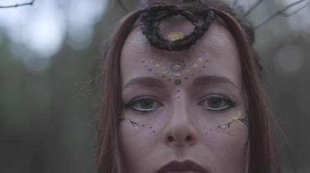 duende : Portrait of an attractive dryad or forest fairy with a wreath of branches on her head and painted the third eye on the forehead dancing under the trees. The ancient ritual of forest creature