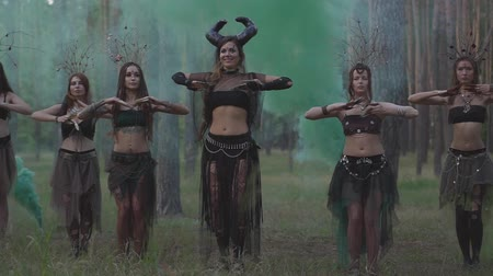 şeytan : Beautiful young women in theatrical costumes of devil or maleficent dancing in forest showing perfomance or making ritual on the background of holi paints Stok Video