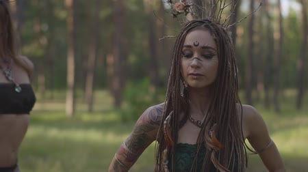 ритуал : Group of women dancers with make-up and in mystical fabulous costumes dancing groovy dance in the forest. Forest fairies, dryads have fun among the trees. Performance of dancers outdoor.