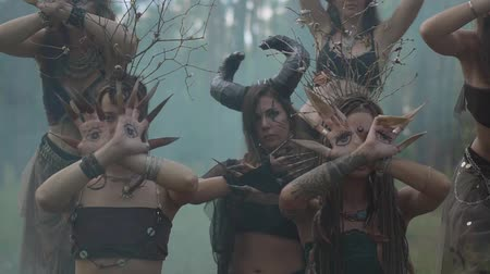 színésznő : Dryads or forest fairies with painted eyes on the palms and false claws moving fingers with long claws in cloud of the smoke. Performance of dancers in the forest. Slow motion