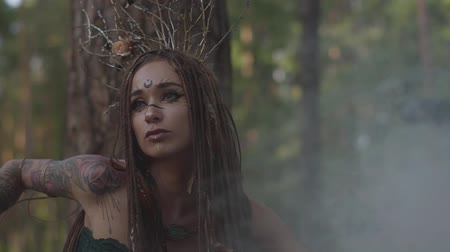 színésznő : Attractive dryad or forest fairy with afro-braids and tattoos on the body dancing in a beautiful costume in the cloud of smoke. The ancient ritual of forest creature. Performance of dancer in the forest. Slow motion