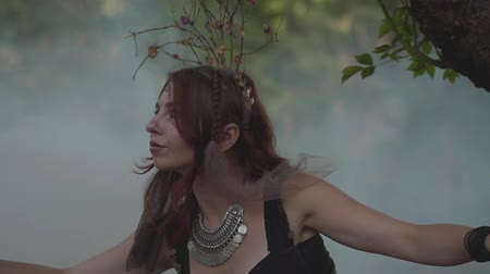 ninfa : Attractive dryad or forest fairy with afro-braids and tattoos on the body dancing in a beautiful costume in the cloud of smoke. The ancient ritual of forest creature. Performance of dancer in the forest. Slow motion