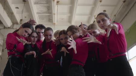 part of clip : Professional dancer girls and boys enjoying hip hop moves performing freestyle dance together in an abandoned building. Crowd in same stage costumes emotionally showing part of performance with hands Stock Footage