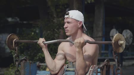 esportivo : An athletic man raising the barbell in the park. Exercise for biceps. Close up portrait. Fitness concept. Healthy lifestyle Stock Footage
