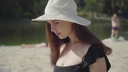 sensuous : Portrait of a young woman in the summer white hat on the beach. People resting at the river in the background. Summer leisure concept. Weekend time