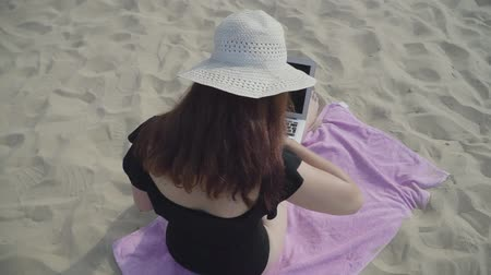sensuous : Back view of a young woman in the summer white hat working with laptop on the beach. Freelance concept. Busy woman on the weekend