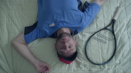 opponent : Handsome tired tennis player in sports equipment is lying on the bed with a tennis racket at the hotel. Stock Footage