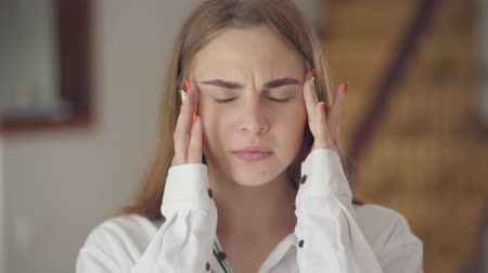 dor de cabeça : Portrait of confident carefree cute woman with different colored eyes looking at camera indoors. Young girl with a headache rubs her head with her hands. Migraine, sick headache