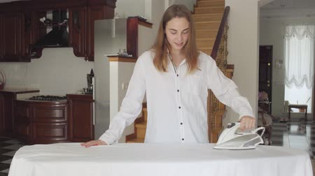 žehlení : Attractive young woman dancing and spinning while doing housework at home. Active positive housewife ironing her clothes on ironing board. Wash Day, washing day