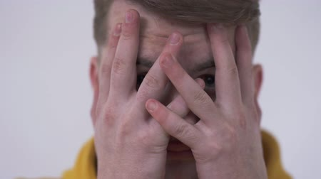 facepalm : Close-up of shy young man looking at the camera from behind fingers covering face with his hands. Concept of hiding emotions