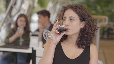 tasting : Young beautiful curly woman drinking red wine at the street cafe. The girl enjoying alcohol relaxing outdoors. The lady sitting at the table looking away Stock Footage