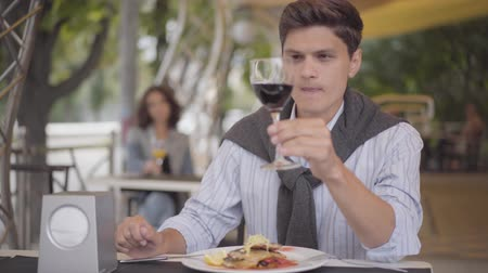 denemek : Young man eating tasty meat food at a street cafe and enjoying elite red wine. The man enjoying his meal relaxing outdoors. The guy cutting cutlet with fork and knife. Leisure outdoors Stok Video