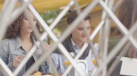részvény : The happy couple enjoying their dinner relaxing in cafe. The curly woman sharing her food with boyfriend. Shooting from behind the fence. Leisure together, date concept