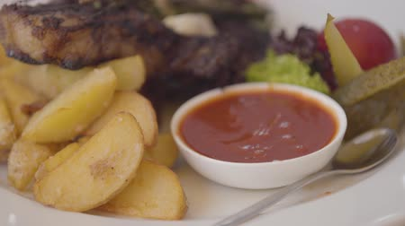chips : Tasty dish on a white plate in an expensive restaurant close-up. Sauce, fried meat and potatoes