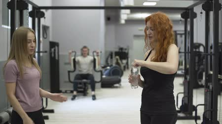 一定の : Positive female trainer giving a bottle of water to the redhaired woman in the gym. The girl working with a personal trainer. Concept of sport, active lifestyle, healthcare 動画素材