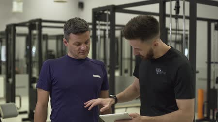 javul : Young professional fitness trainer with a tablet in hands explaining plane of training for a new client. The man going to improve his press in the gym. Body care. Concept of sport, active lifestyle, healthcare Stock mozgókép