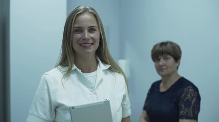 сосредоточиться на переднем плане : Beautiful caucasian doctor smiling in the foreground looking at the camera while her mature patient sitting in the background. Concept of healthcare, treatment, recreation, medicine. At the doctors office Стоковые видеозаписи