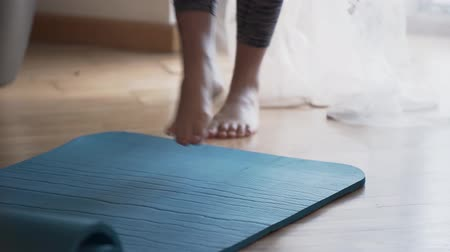 dobrado : The woman unrolling a yoga mat lying on the floor using her foot. The girl preparing for yoga lesson or meditation at home or in the studio. Healthy lifestyle