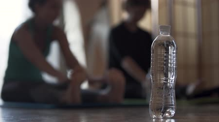 сложить : Two out of focus girls doing exercises while sitting on the floor. Bottle of water in the foreground. Healthy lifestyle, recreation, keeping in shape