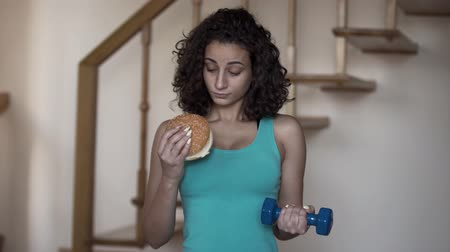 сомнение : Portrait of attractive slim lady holding a big burger and a small dumbbell in hands trying to choose between a healthy lifestyle and tasty food. Choice, dilemma concept Стоковые видеозаписи