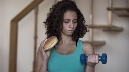 сомнение : Portrait of cute curly young woman holding a big burger and a small dumbbell in hands trying to choose between a healthy lifestyle and tasty food. Choice, dilemma concept Стоковые видеозаписи