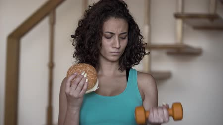 難しさ : Portrait of cute curly young woman holding a big burger and a small dumbbell in hands trying to choose between a healthy lifestyle and tasty food. Choice, dilemma concept 動画素材
