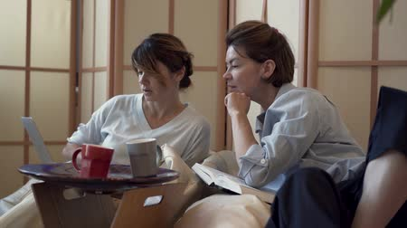 aesthetics : Two adult women with spending time at home together drinking tea or coffee watching a movie on laptop. Two elegant mature girlfriends relaxing at home. Concept of friendship, wellness, happy life Stock Footage