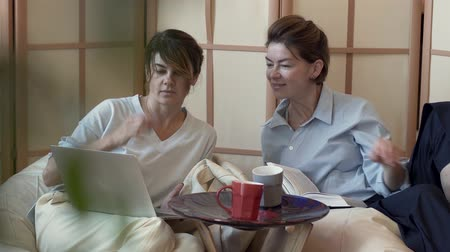 aesthetics : Two adult women spending time at home together drinking tea or coffee watching information on laptop. Two elegant mature girlfriends look at laptop screen. Concept of friendship, happy life Stock Footage