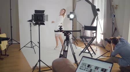 fotografando : Backstage of the photo shoot. Professional photographer taking photos of elegant woman dancing and spinning on white background in the studio. Fashion magazine studio photoshoot