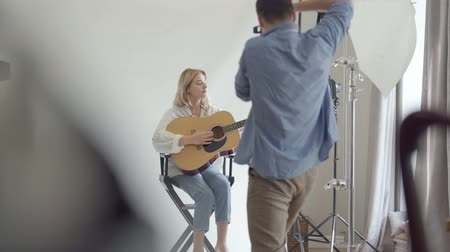 fotoshoot : Backstage of the photo shoot. Famous professional photographer taking photos of young woman playing guitar while sitting on the chair on white background in the studio. Fashion studio photoshoot Stockvideo
